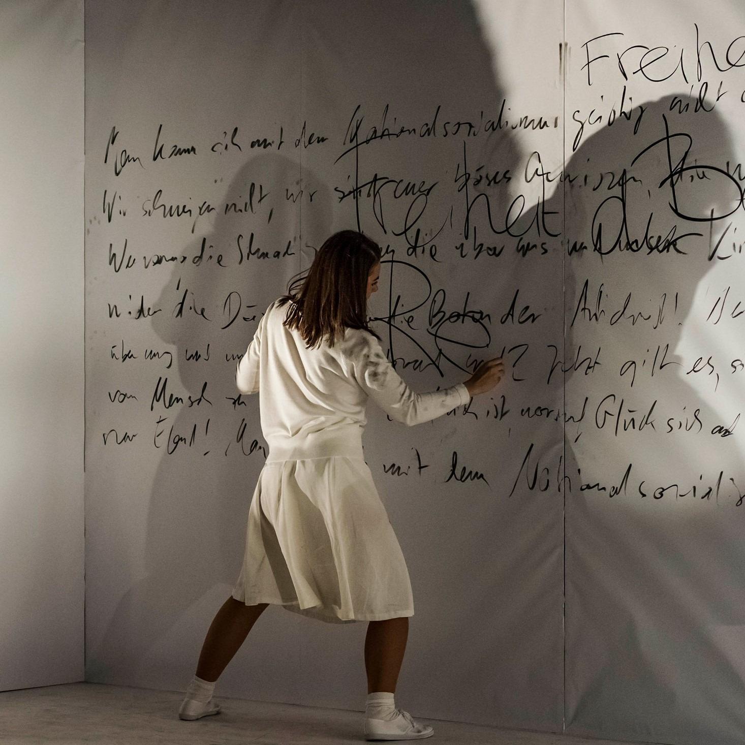 Frau vor einer beschrifteten Wand