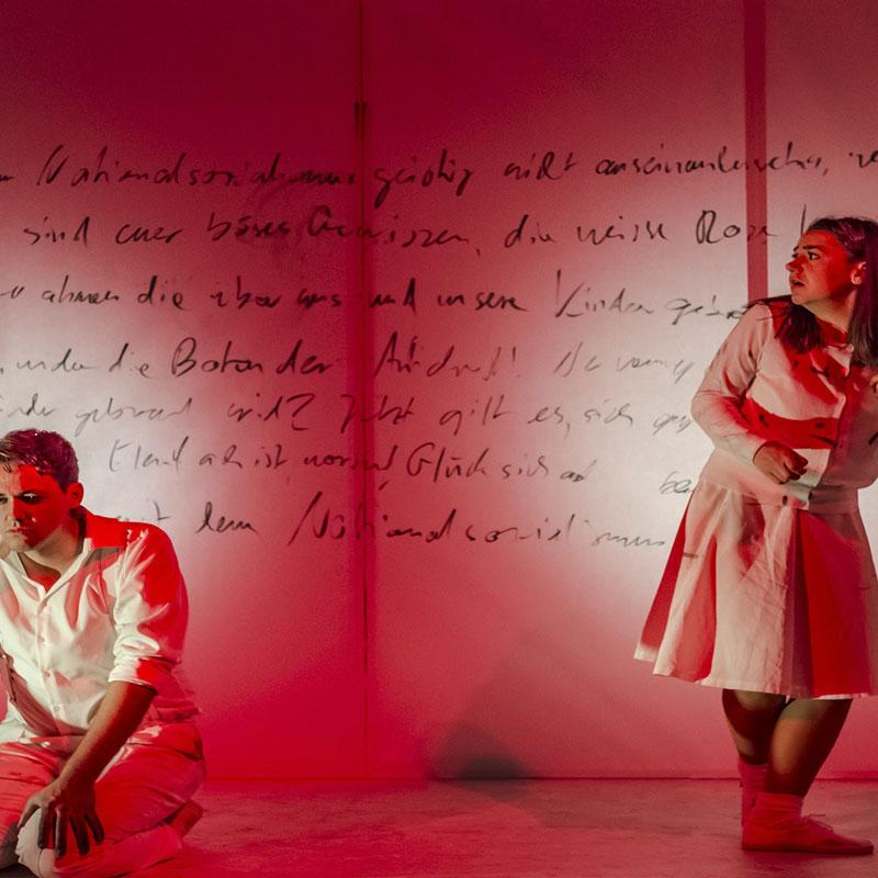Zwei Personen vor einer beschrifteten Wand. Theater-Aufnahme