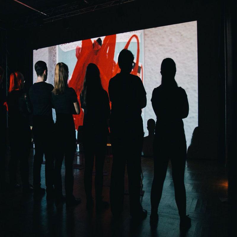 Personengruppe als Silhouette vor einer hellen Projektion