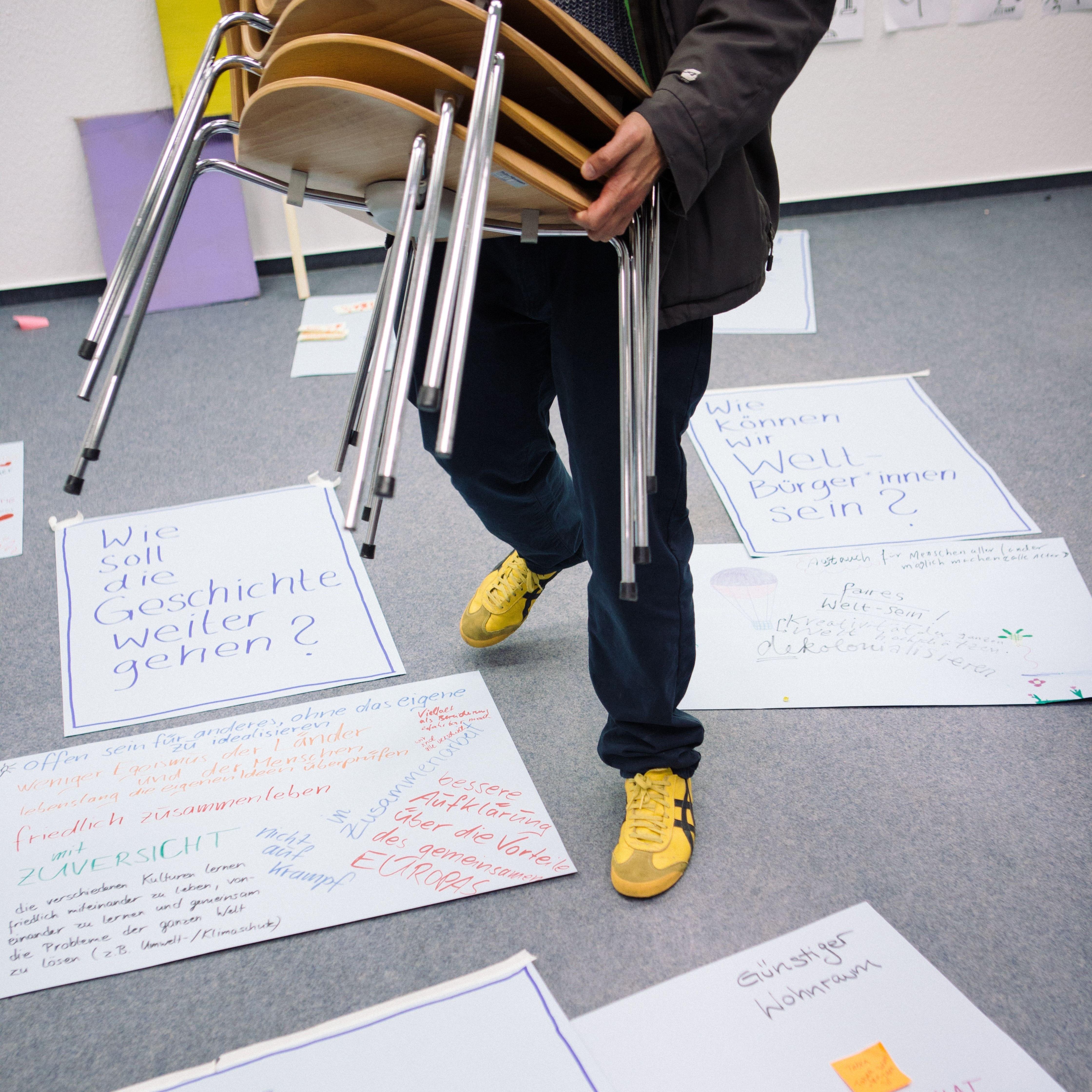 Person mit Stühlen in den Händen