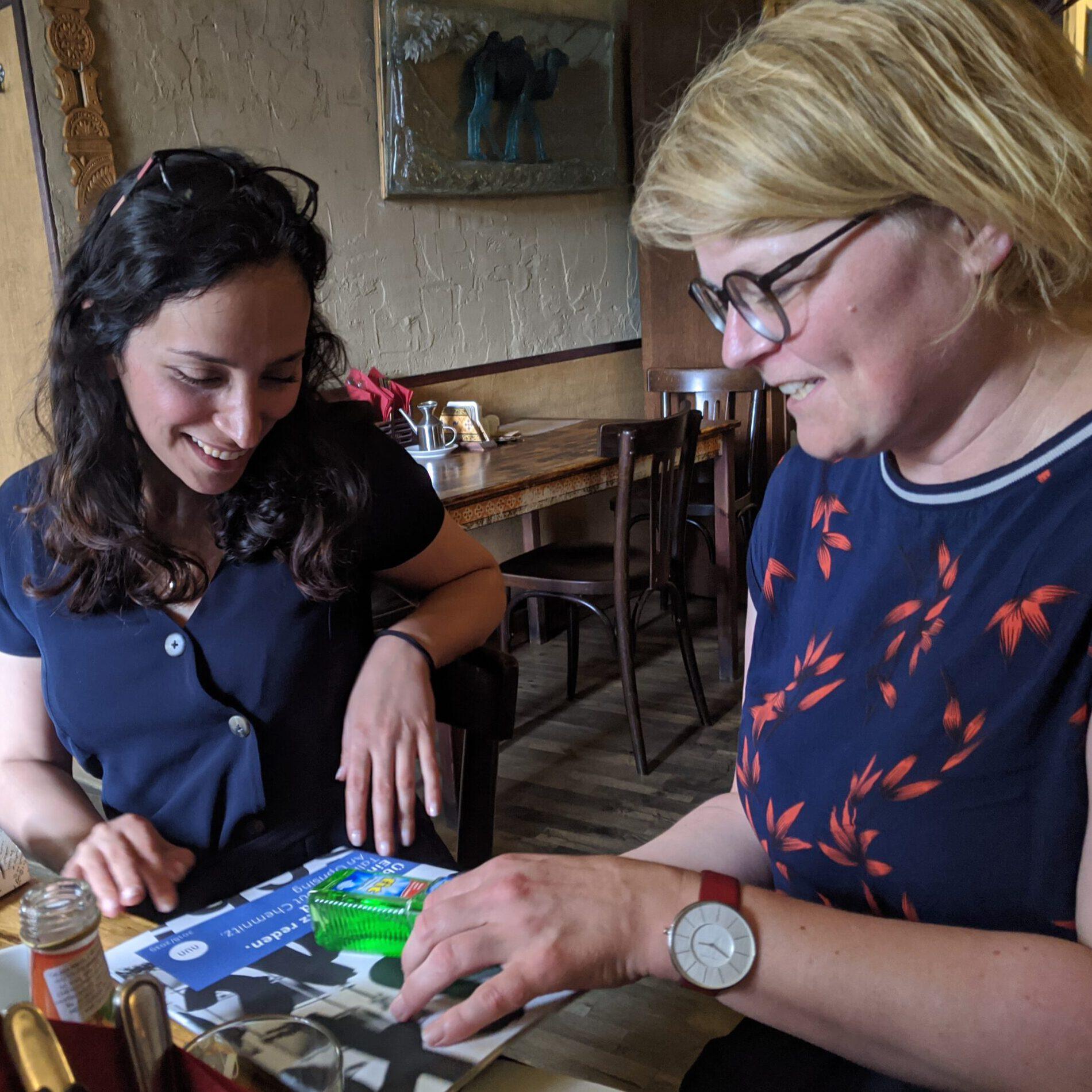 Zwei Frauen schauen sich Broschüre an