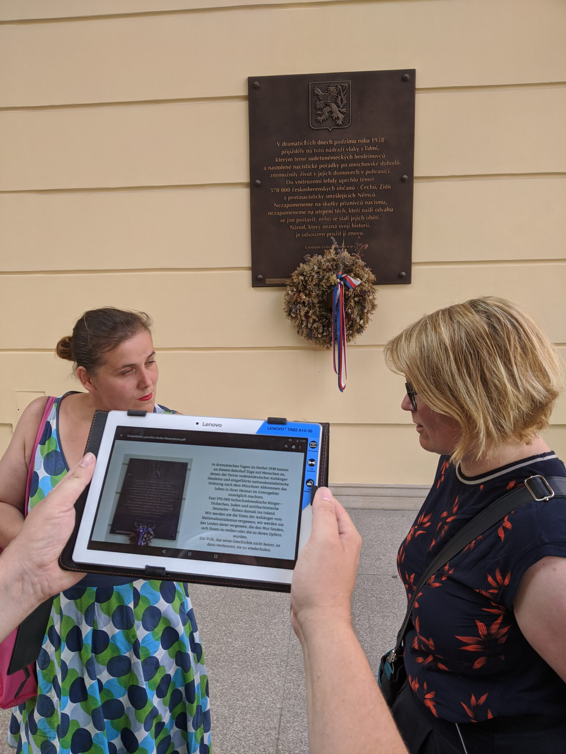 Zwei Frauen unterhalten sich vor einer Gedenkplatte in Prag.