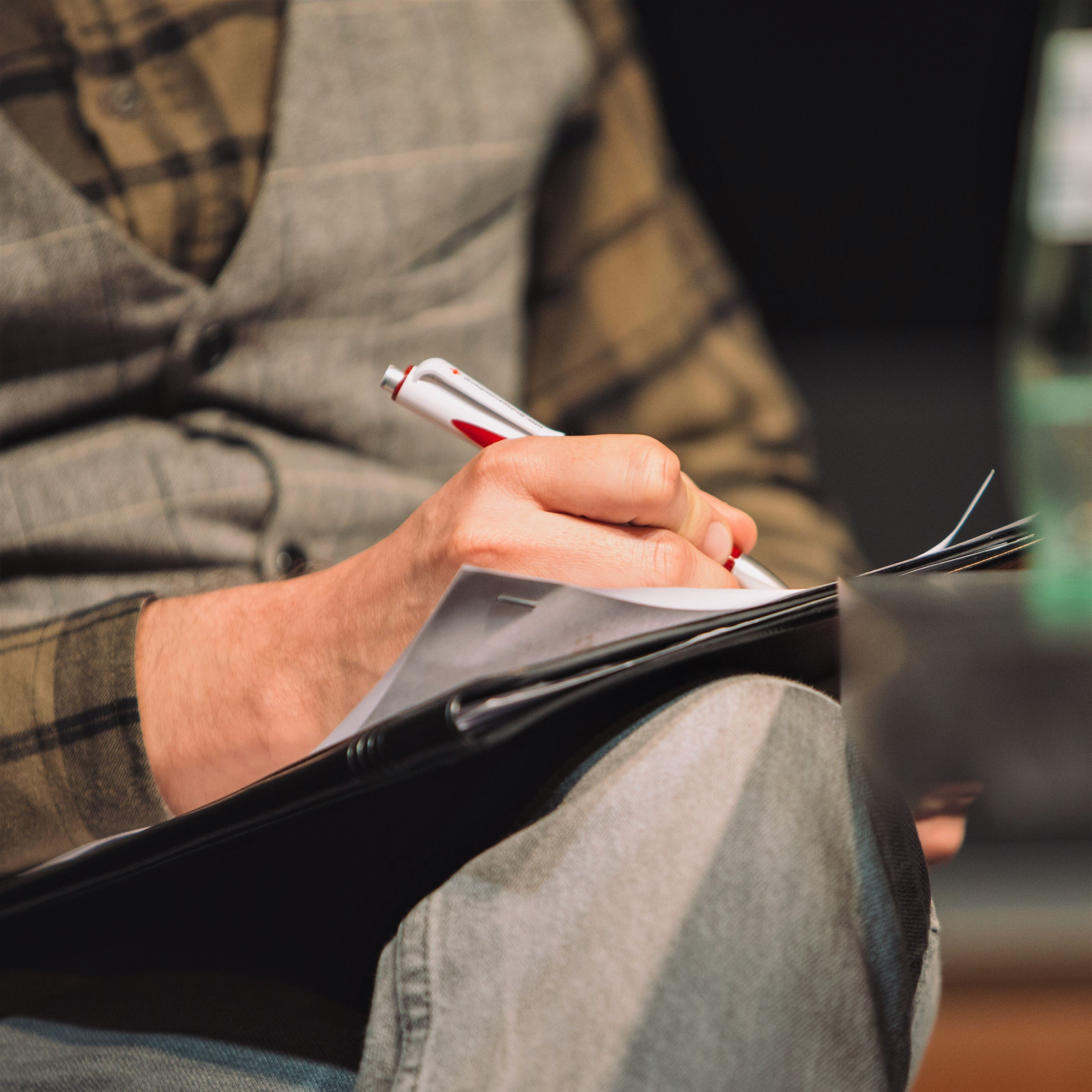 Person schreibt etwas in seine Notizen